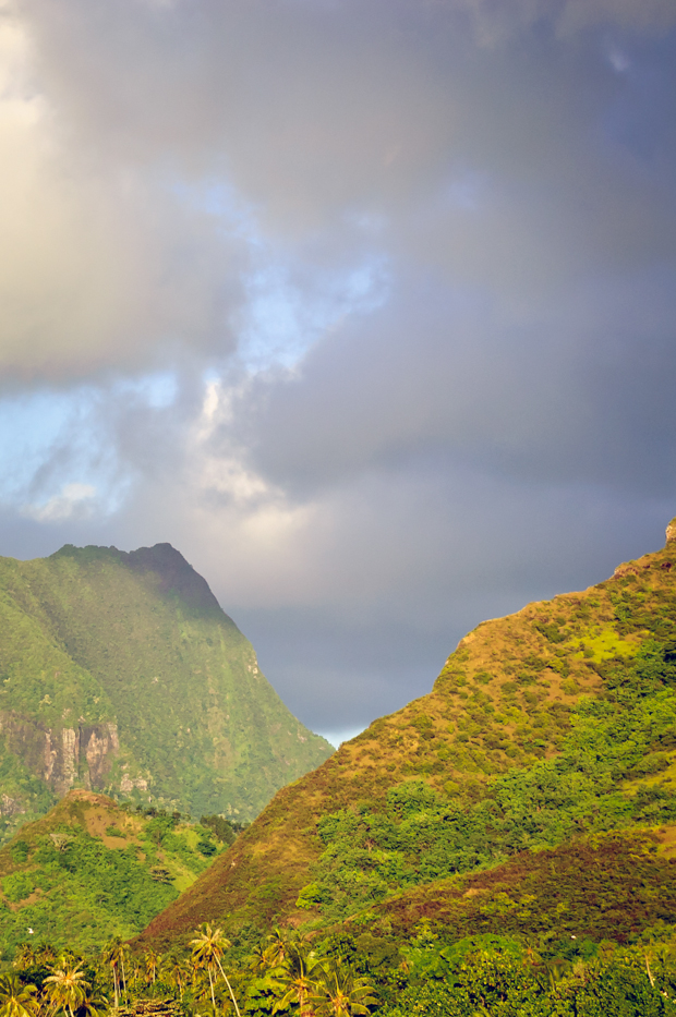 travel photograph of green mountains, clouds, and sky in tahiti