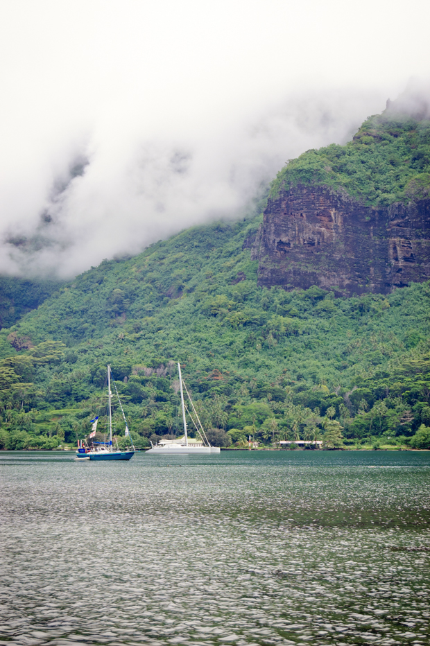 travel image of boats, green mountains, and mist from tahiti