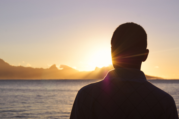 silhouette of man in front of setting sun in tahiti