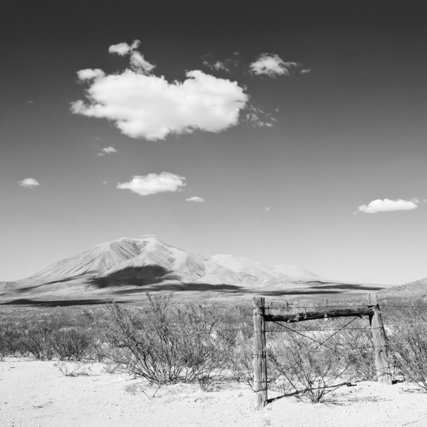 black and white image of mountains and fence in the west texas dessert
